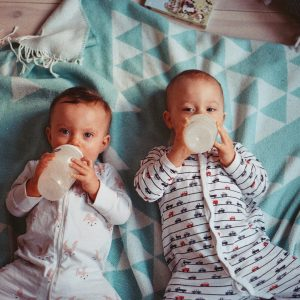 this is two babies laying on a swaddle blanket with bottles